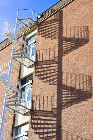 Spiral fire escpa staircase on a building with dramatic shadows photo