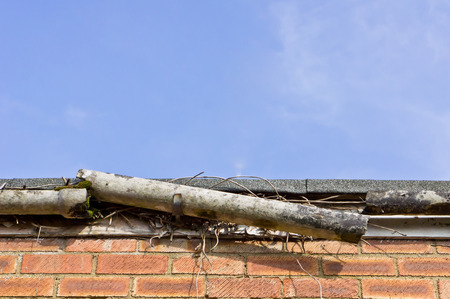 damaged roof: A broken plastic gutter on the roof of a house