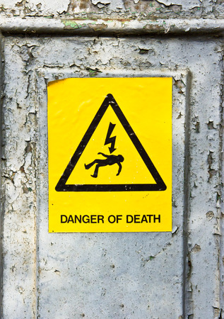 deadly danger sign: Yellow danger of death sticker on a rusty metal surface
