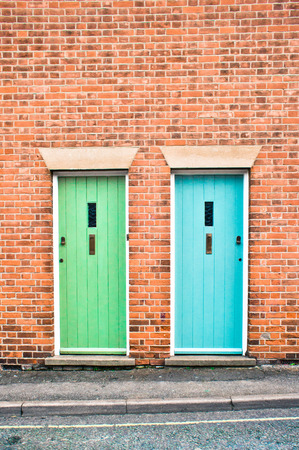 Blue and green front doors in adjoining houses Stock Photo