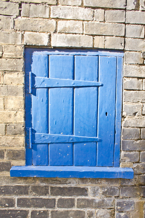 cubby: Old small blue wooden door in a brick wall