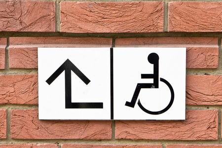 Sign for wheelchair access on a brick wall photo