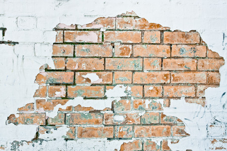 Peeling white paint on a brick wall as a background
