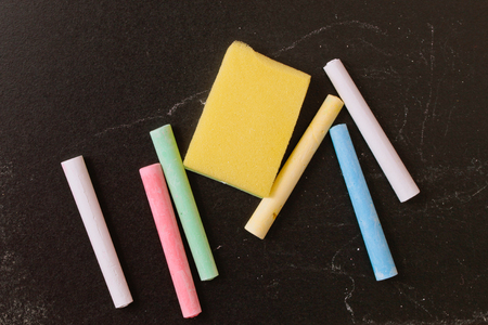 pieces of chalk against a black chalk board with a sponge wiper photo