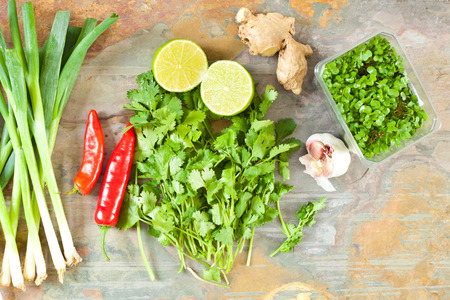 Fresh coriander, ginger, lime, chilli and spring onions with a punnet of cress photo