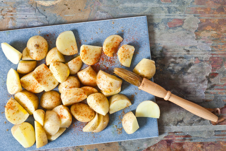 stone worktop: Raw chopped potatoes being brushed with oil for roasting with paprika seasoning Stock Photo