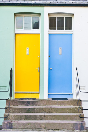 adjacent: Yellow and blue front doors of neighboring homes