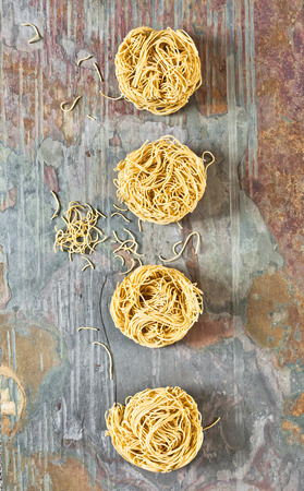 stone worktop: Balls of dried egg noodles on a stone worktop Stock Photo
