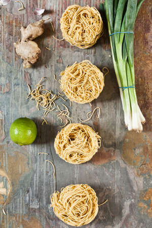 stone worktop: Balls of dried egg noodles with spring onions, ginger and lime, on a stone worktop