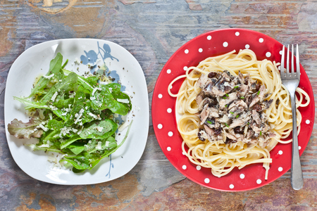 side salad: Sardines and raisins with spaghetti on a red plate on a stone table with a side salad