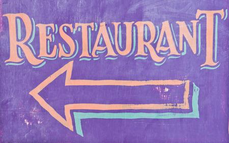 A purple restaurant sign with an arrow photo