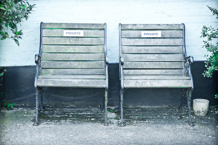 reserved seat: Two wooden garden seats with private signs on them