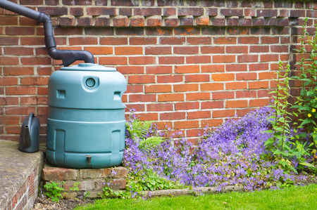 A water butt in a garden against a red brick wall