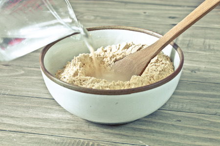Water being poured into a bowl of flour for makign dough