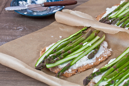 bases: Pizza bases with ricotta cheese and asparagus ready for baking