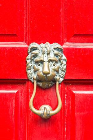 A classic antique lion door knocker on a red door photo