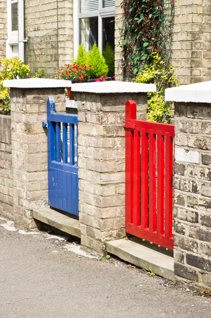 neighboring: Red and blue gates at the front of neighboring english houses