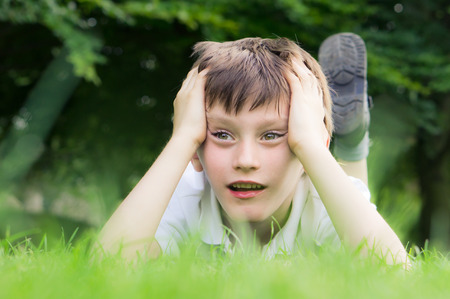 fascination: A six year old boy lying on the grass staring at something of interest Stock Photo