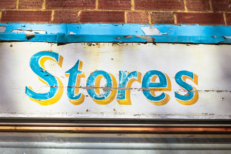 general store: Sign for stores on a weathered wooden board Stock Photo