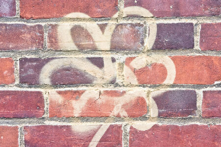 asbo: A flower spray-painted on a red brick wall