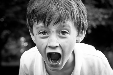 A dramatic monochrome image of an angry six year old boy