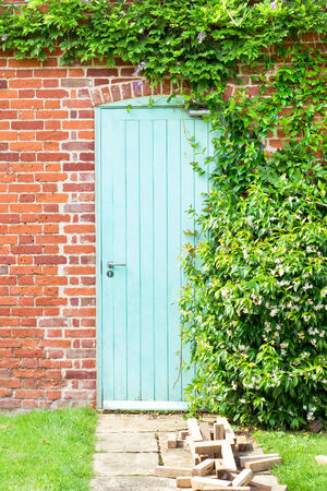A blue wooden door in a red brick wall photo