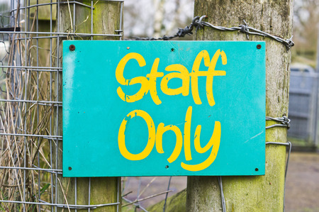 wooden post: Green staff only notice on a wooden fence post