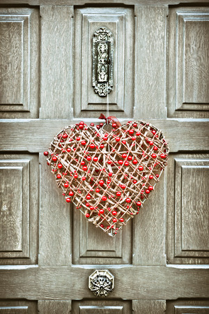 A heart shaped christmas wreath on a wooden front door photo