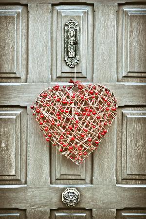 A heart shaped christmas wreath on a wooden front door Standard-Bild