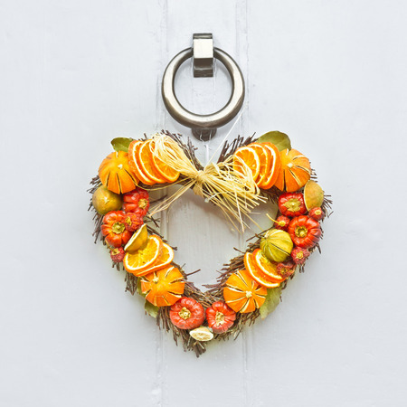 A heart shaped fruit christmas wreath on a wooden front door photo