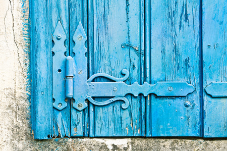 wicket door: Decorative hinge on an old blue wooden window shutter