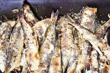 seafish: Grilled sardines with fresh herbs on a black plate