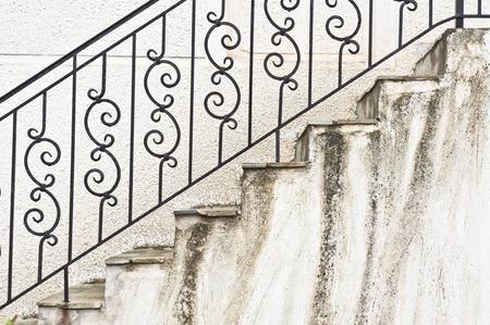 bajando escaleras: Escalones de piedra y barandillas de hierro
