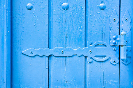 hinge joint: Decorative hinge on a blue painted wooden door with rain drops