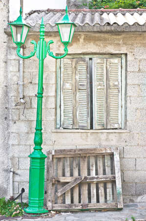 lamp post: Old house in Greece with wooden shutters and a green lamp post Stock Photo
