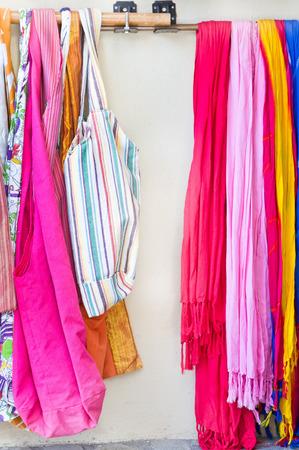 bufandas: Bufandas y bolsos vibrantes en un estante en una tienda