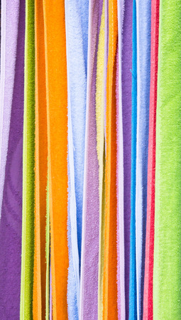 Colorful plain towels hanging as a background image photo
