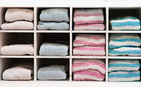 whitem: Selection of warm winter ladies jumpers on a shelving unit Stock Photo