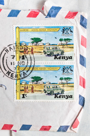 franked: BURY ST EDMUNDS, UK- OCTOBER 15 2014:  Two Kenyan postage stamps from 1977 on an airmail envelope Editorial