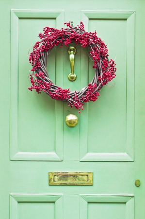 festive pine cones: A red berry wreath on a front door Stock Photo