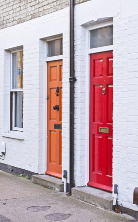 neighbouring: Red and orange front doors on adjoining terraced homes in the UK Stock Photo