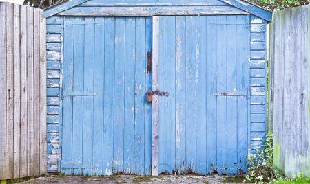 upkeep: A weathered blue woooden garage door Stock Photo