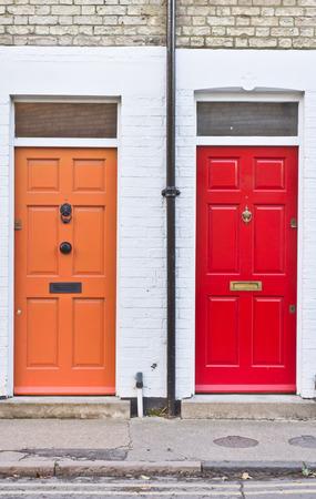 cerrar puerta: Puertas delanteras de color naranja en casas adosadas contiguas en el Reino Unido y la Red