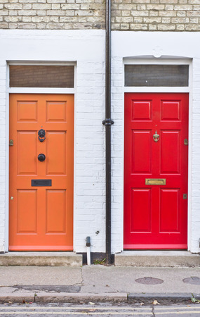 Red and orange front doors on adjoining terraced homes in the UK Stock Photo