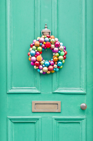 A colorful christmas wreath on a green front door Stock Photo