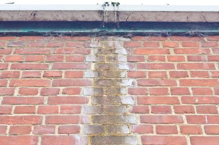 limescale: Long term damp brickwork caused by a leaking gutter Stock Photo