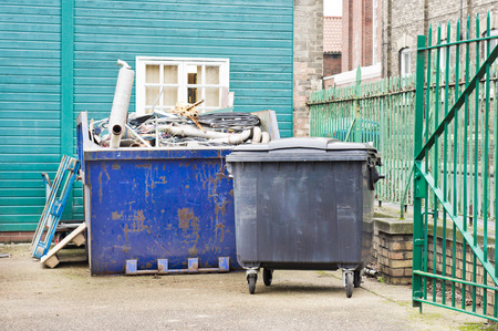 A waste skip and a large bin at a building site