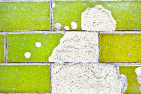 underlying: Broken green tiles revealing underlying grout Stock Photo