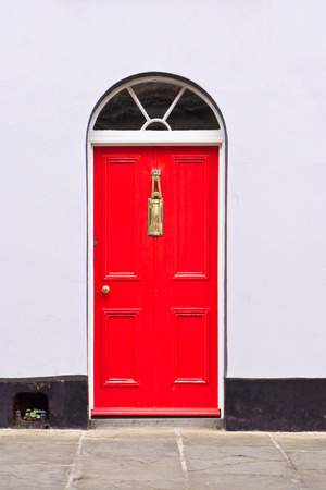Red front door in an english town house