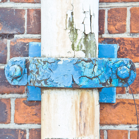 outflow: Close up of a blue rusty clip on a white drainpipe